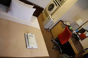 Photo de la chambre du Tokyu Stay Gotanda avec le lit et la machine à laer