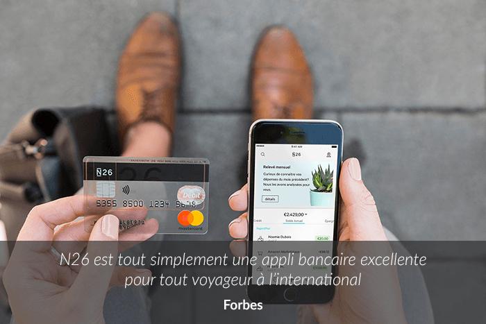 Photo montrant une personne qui tient une carte bancaire N26 et un smartphone en main