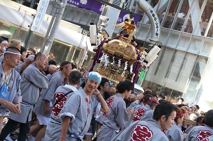 Festival de quartier avec des gens qui portent un sanctuaire portatif dans le quartier de Shibuya à Tokyo